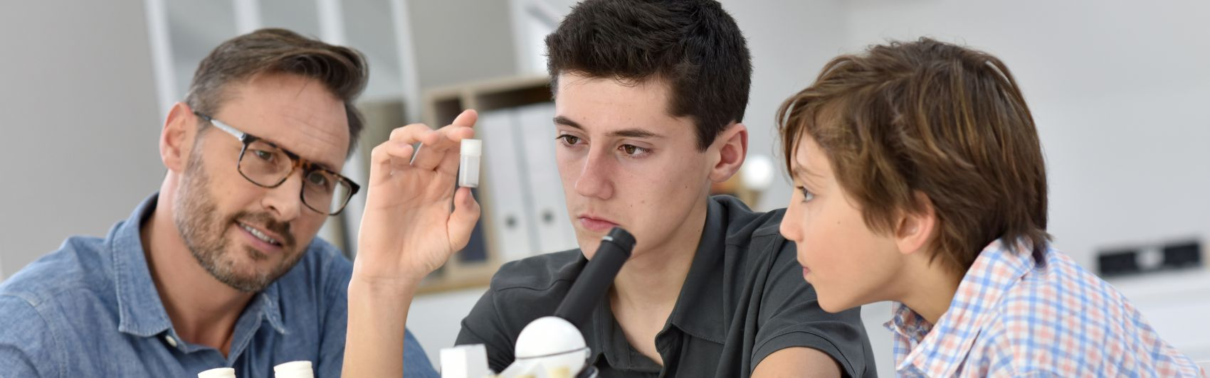 Schüler diskutieren mit einem Lehrer über einen Versuch